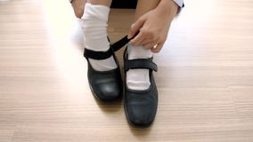 Asian Thai schoolgirl student in high school uniform is wearing her black leather shoes in cute education fashion design on the wo stock video footage