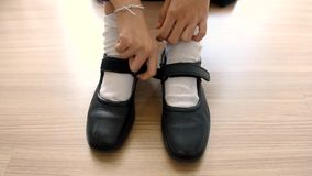 Asian Thai schoolgirl student in high school uniform is wearing her black leather shoes in cute education fashion design on the wo stock footage