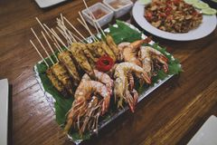Asian Thai snacks are located on a plate standing on a wooden table. There are shashliks on skewers, fried shrimps and vegetables. The plate is lined with Stock Image