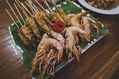 Asian Thai snacks are located on a plate standing on a wooden table. There are shashliks on skewers, fried shrimps and vegetables. The plate is lined with Royalty Free Stock Photography