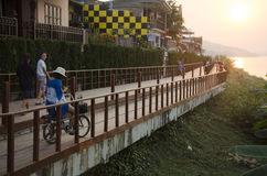 Asian thai woman posing with bicycle and travelers people walking relax at riverside Mekong river in Chiang Khan at sunset Royalty Free Stock Photo