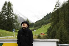 Asian thai woman travel and posing for take photo with Alps mountain at petrol station Stock Photo