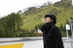 Asian thai woman travel and posing for take photo with Alps mountain at petrol station Stock Photos