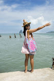 Asian thai woman traveling and posing at harbour with sea and sk Royalty Free Stock Images