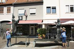 Asian thai women traveler posing with bronze statue for take photo. At Marktplatz or market place of Ladenburg on August 28, 2017 in Baden-wurttemberg, Germany Royalty Free Stock Photography