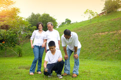 Asian three generation family. Inspecting leaf with magnifying glass in the park. Healthy lifestyle concept Royalty Free Stock Images
