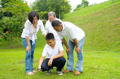 Asian three generation family. Inspecting leaf with magnifying glass in the park. Healthy lifestyle concept Stock Photo