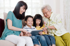 Asian three generations family. Having fun with tablet computer Royalty Free Stock Image