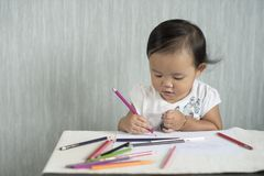 Asian toddler / baby girl is having fun learning to use pencils. Stock Photo