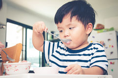Asian toddler boy eating on high chair Royalty Free Stock Photo