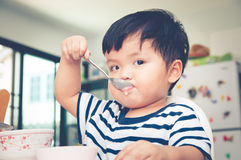 Asian toddler boy eating on high chair Stock Photos