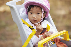 Asian toddler girl in a child bike seat looking to camera Royalty Free Stock Photo
