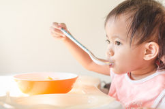 Asian toddler girl eating cereals with milk on high chair at hom Stock Photography