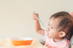 Asian toddler girl eating cereals with milk on high chair at hom Royalty Free Stock Photo