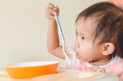 Asian toddler girl eating cereals with milk on high chair at hom Stock Image