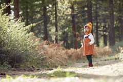 Asian toddler girl walking alone in a forest, side view Stock Photo
