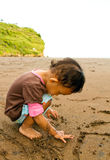 Asian toddler girl writing on beach sand Stock Photos