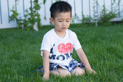 Asian toddler playing on the green grass Stock Photos