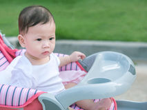 Asian toddler sit in stroller outdoor morning. Stock Photos