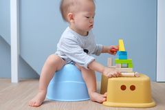 Asian toddler sitting on potty while playing wooden blocks, potty training concept Stock Photos
