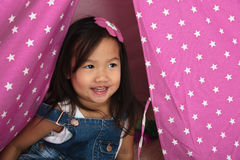 Asian toddler smiling and playing in pink tent Royalty Free Stock Images