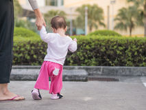 Asian toddler walking first step in park morning. Stock Image