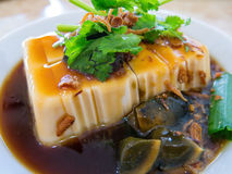 Asian Tofu with Century Egg. A SE Asian dish of fresh tofu served chilled and accompanied with century egg, fried shallots and Chinese parsley in a soya-based stock image