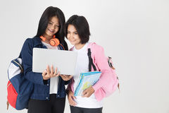 Asian tourism female concept. Tourism, travel, leisure, concept - smiling teenage girls with map and laptop on gray background Stock Images