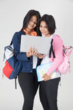 Asian tourism female concept. Tourism, travel, leisure, concept - smiling teenage girls with map and laptop on gray background Royalty Free Stock Photos