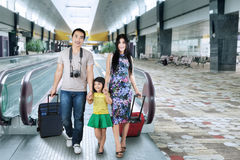 Asian tourist arrive in airport. Three member of asian tourist walking on escalator in the airport hall Stock Photo