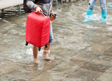 Asian tourist barefoot in the water with her luggage. Venice, It Royalty Free Stock Photos