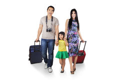 Asian tourist carrying luggage. Three member of asian tourist walking in studio while carrying luggage Stock Image