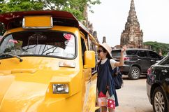 Asian tourist girl query for the way with old man driver taxi. Or tuk tuk touring,parking lot in front of Wat Chaiwatthanaram at Ayutthaya,Thailand royalty free stock photos