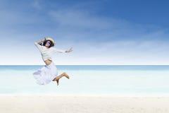 Asian tourist jump at white sand beach Stock Photos