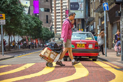 Asian tourist with luggage. Hong Kong, China - December 6, 2016: asian male tourist with luggage side walking the Times Square intersection, largest shopping Stock Photos