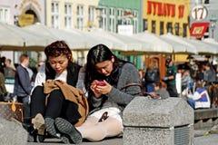 Asian Tourist in Nyhavn in Copenhagen. Asian girls sit using phone in Nyhavn in copenhagen, on a sunny day Royalty Free Stock Photo