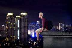 Asian tourist sitting on the building rooftop in the city at night. Asian tourist sitting on the building Royalty Free Stock Images