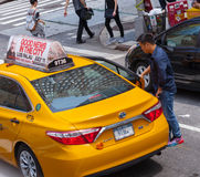 Asian tourist takes the yellow cab in Manhattan, NYC. NEW YORK CITY, NY, USA - JULY 07, 2015: Asian tourist takes the yellow cab in Manhattan, NYC. The taxicabs Stock Photo