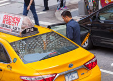 Asian tourist takes the yellow cab in Manhattan, NYC. NEW YORK CITY, NY, USA - JULY 07, 2015: Asian tourist takes the yellow cab in Manhattan, NYC. The taxicabs Royalty Free Stock Image