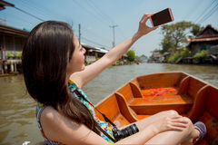 Asian tourist taking self-portrait photo. Asian tourist in Damnoen Saduak floating market taking self-portrait photo smiling happy showing with river in Royalty Free Stock Photography
