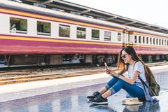 Asian tourist teenage girl at train station using smartphone map, social media check-in, or buy ticket booking. Modern travel app technology, lone traveler Stock Photos