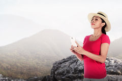 Asian tourist wearing hat holding cellphone Stock Images