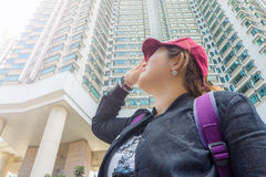 Asian tourist woman with hot sunny day at noon. She is in front of high rise building Royalty Free Stock Images