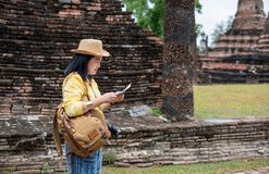Asian tourist woman see map at ancient of pagoda temple thai architecture at Sukhothai,Thailand. Female traveler in casual thai. Cloths style visiting city royalty free stock photography