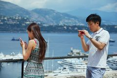 Asian tourists check travel photos at the viewpoint in Monaco. Royalty Free Stock Images