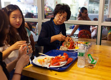 Asian tourists eating fresh lobsters in Chelsea Market. Royalty Free Stock Photos