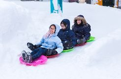 Asian tourists enjoying their time on playing snow slider stock image