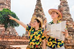 Asian tourists with floral shirts using map to find attraction in old temple ruins. Couple go sightseeing in Wat Chaiwatthanaram, Ayutthaya Historical Park royalty free stock images