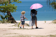 Asian tourists with hot sun on the beach. Royalty Free Stock Photo