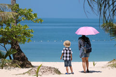 Asian tourists with hot sun on the beach. Royalty Free Stock Image